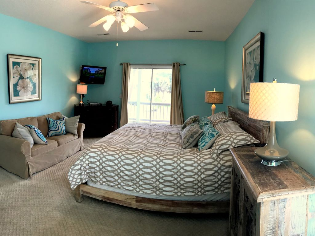 Master Bedroom w/ private entrance to the screen porch, King Bed & sitting area.