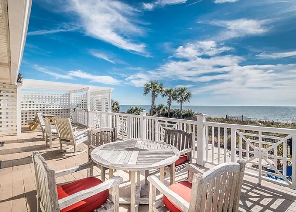 Large sundeck with two dining choices and views of the beach and pool