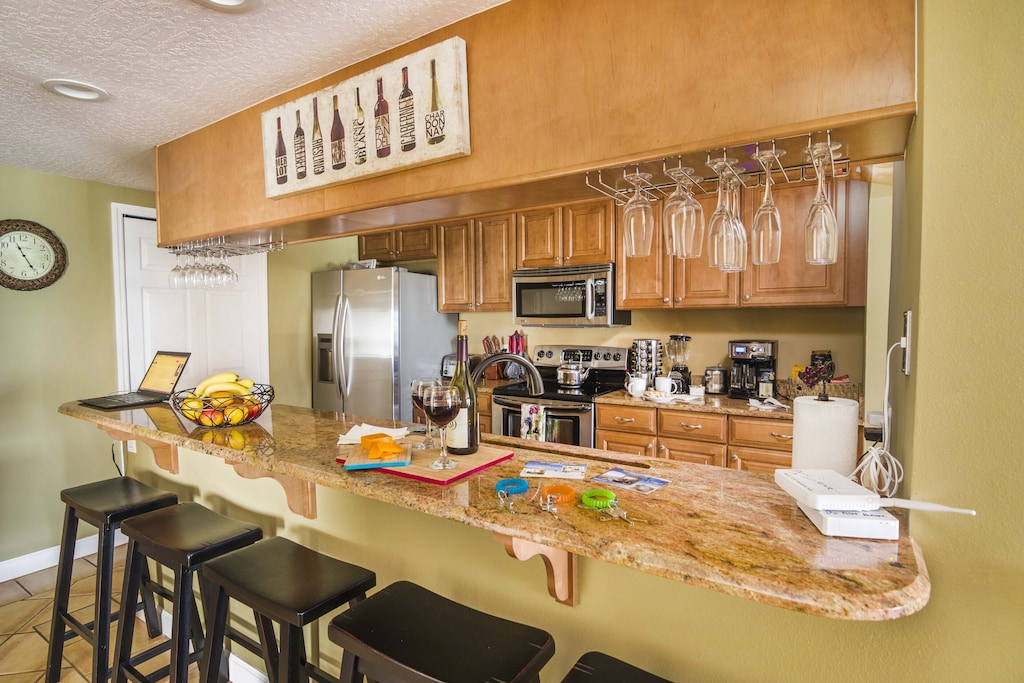 Upscale Kitchen with Granite Counters, Wine Rack and Lunch Bar that Seats 5