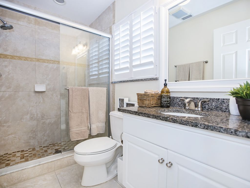 Master bathroom with grant countertops and a walk-in shower