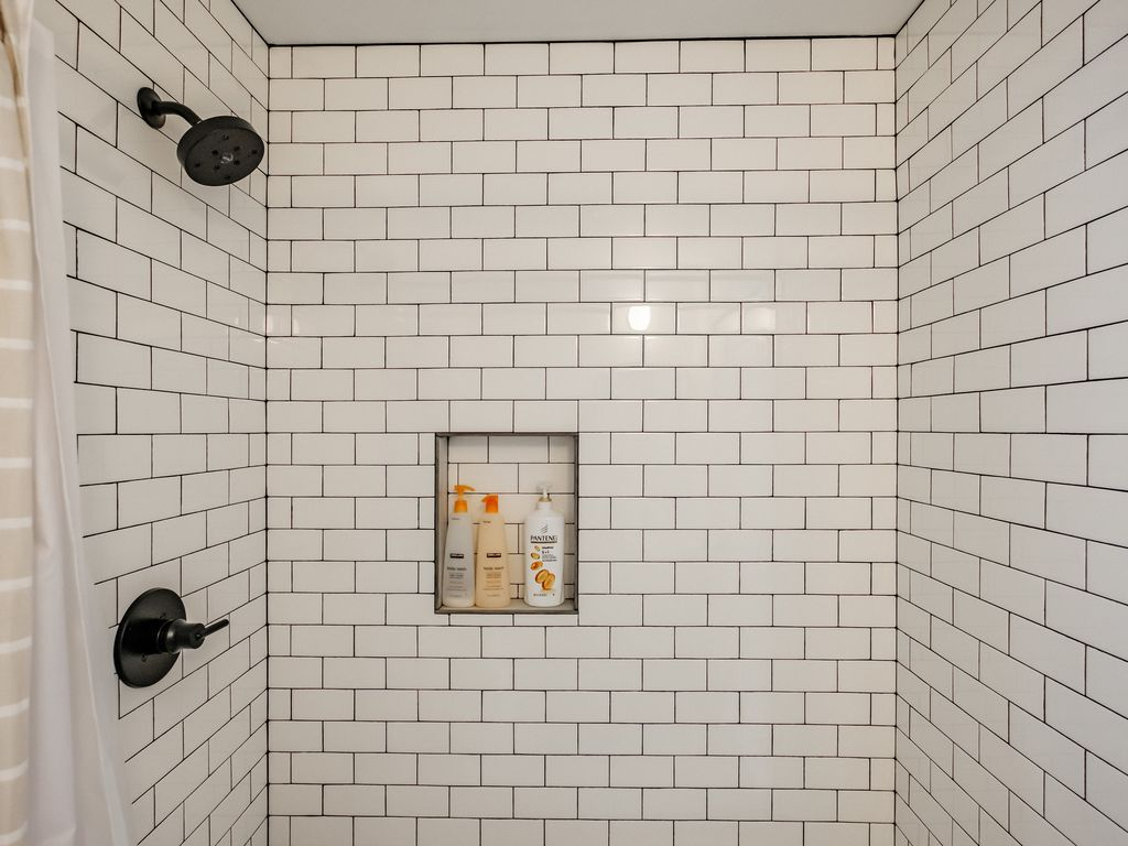 Black & white extends to the honeycomb tiled lower level shower suite.