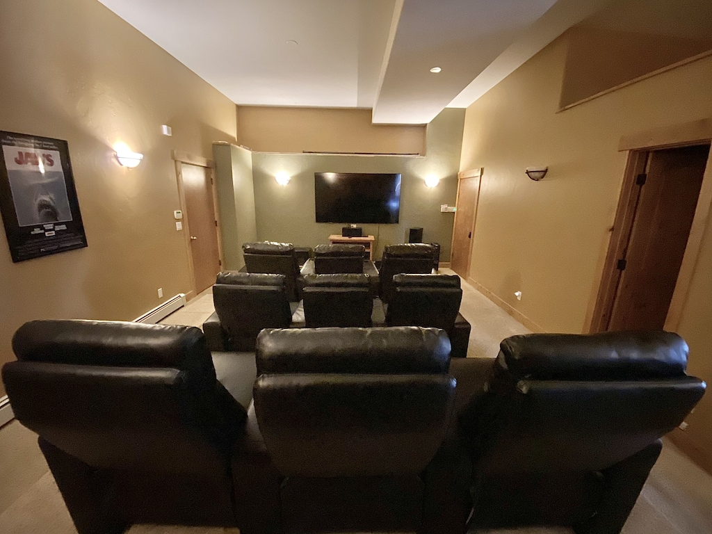 Media Room - Lower level media room with 86 inch, 4K TV with surround sound speakers, 9 reclining chairs