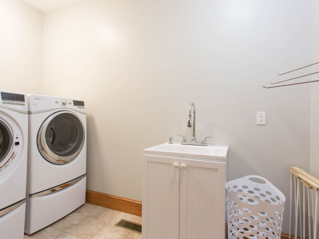 There is a laundry room with a full-size washer/dryer, sink, hangers, laundry basket, and drying rack.