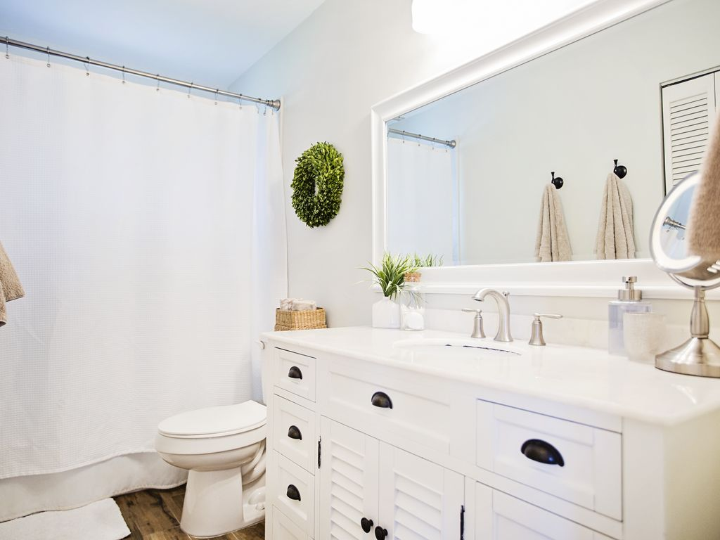 Cottage style master bathroom with bathtub and rain shower.