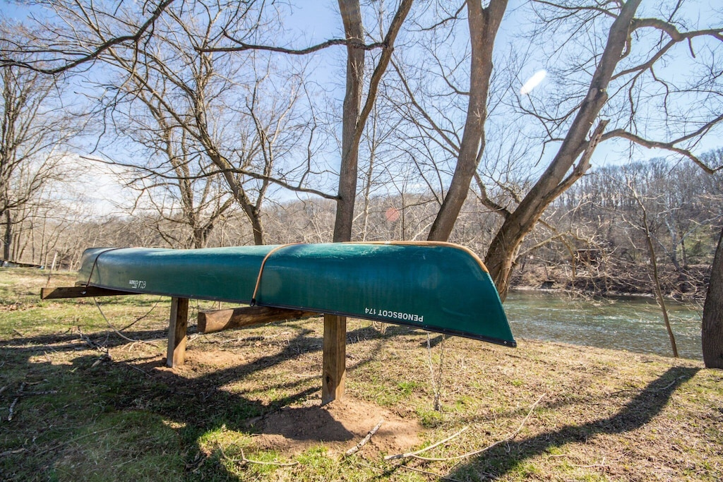 Two canoes on rack located just a few feet from the river