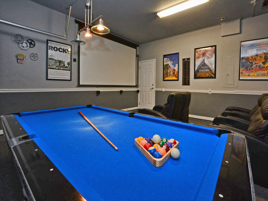 Game room with billiards and an overhead projector for watching movies.