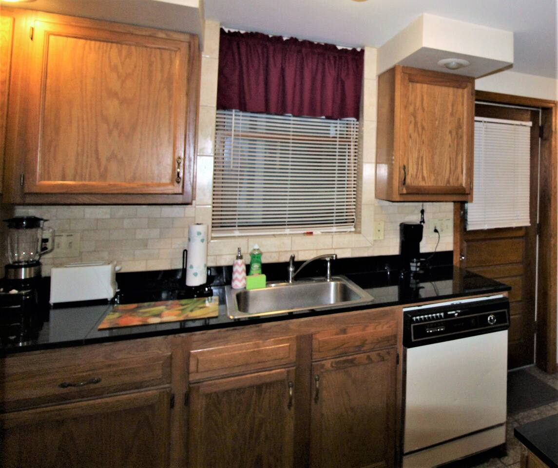 Kitchen with granite countertops and flooring.  Lots of appliances for all the comforts of home
