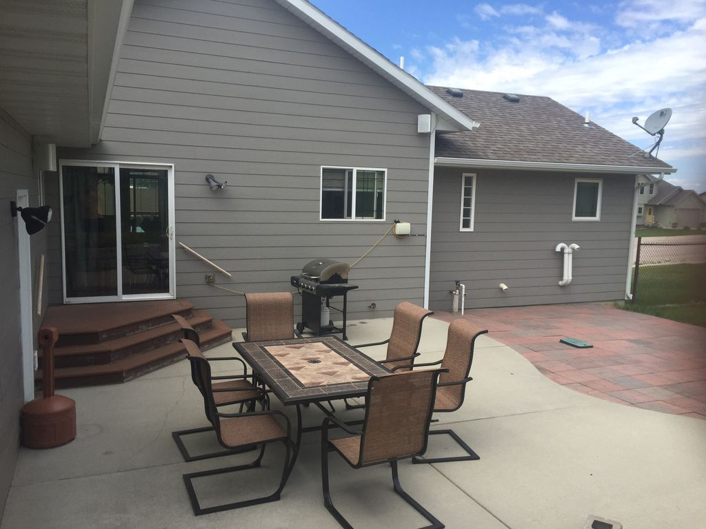 Patio with grill, patio set and smoker pole.