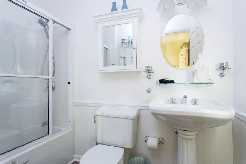 The full bath has a pedestal sink, tub/shower combo with sliding doors, and lovely Colonial-style chrome hardware.
