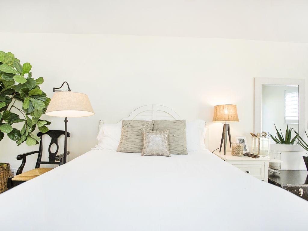 Helles Gästezimmer mit einem Doppelbett und hochwertiger Bettwäsche.
