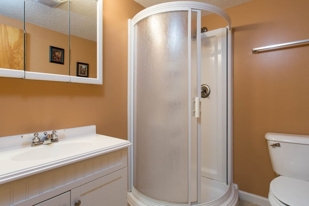 The bathroom has a single vanity and walk-in shower.