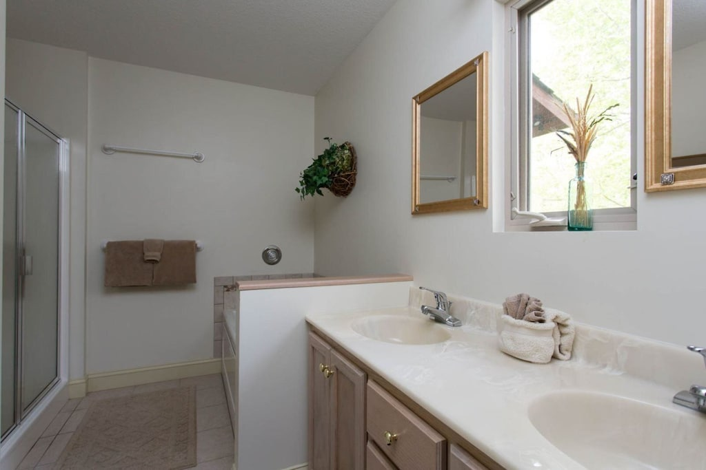 The private adjoining bath has a double vanity, walk-in shower, and jetted tub.