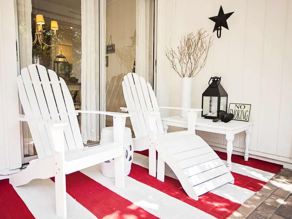Screened in patio area with two adirondack lounge chairs.