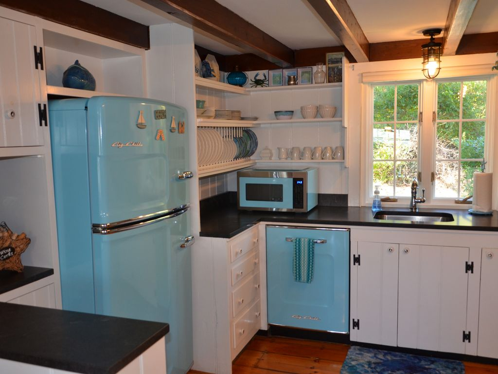 Beach blue vintage style appliances grace the open and airy kitchen.