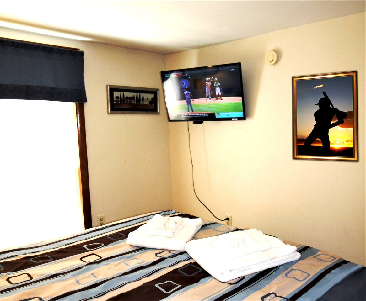 Bedroom with queen size bed and flat screen smart Roku TV