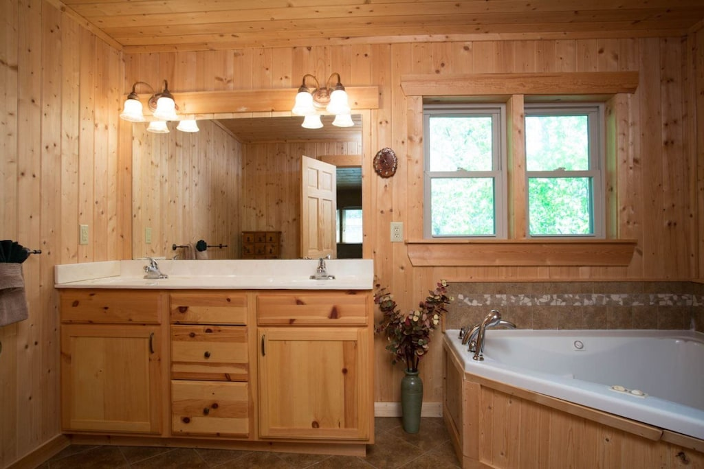 The bathroom has a double vanity and jetted walk-in bathtub.
