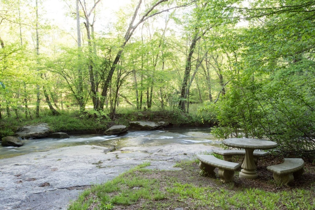 Riverbend amenities - This stone dining set by the river is a perfect place for a meal.