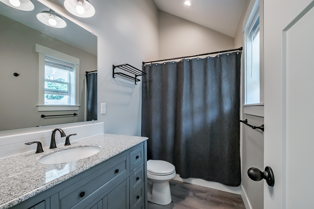 Full bathroom with shower shared between den and kids' room.