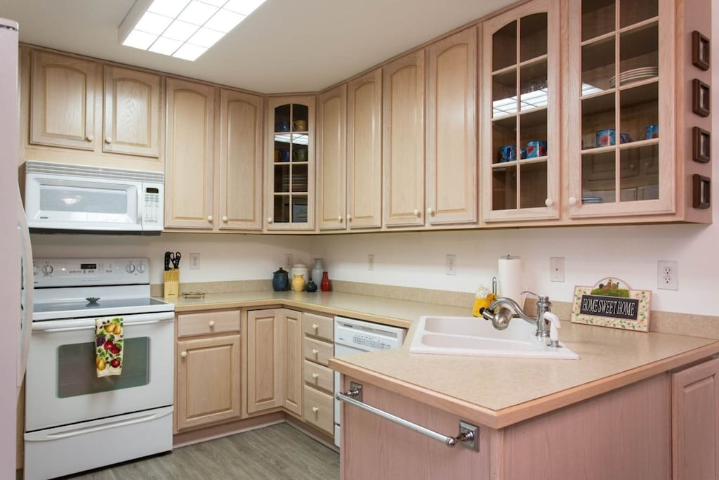 Above the smooth-top electric range is a microwave and there is also a dishwasher.