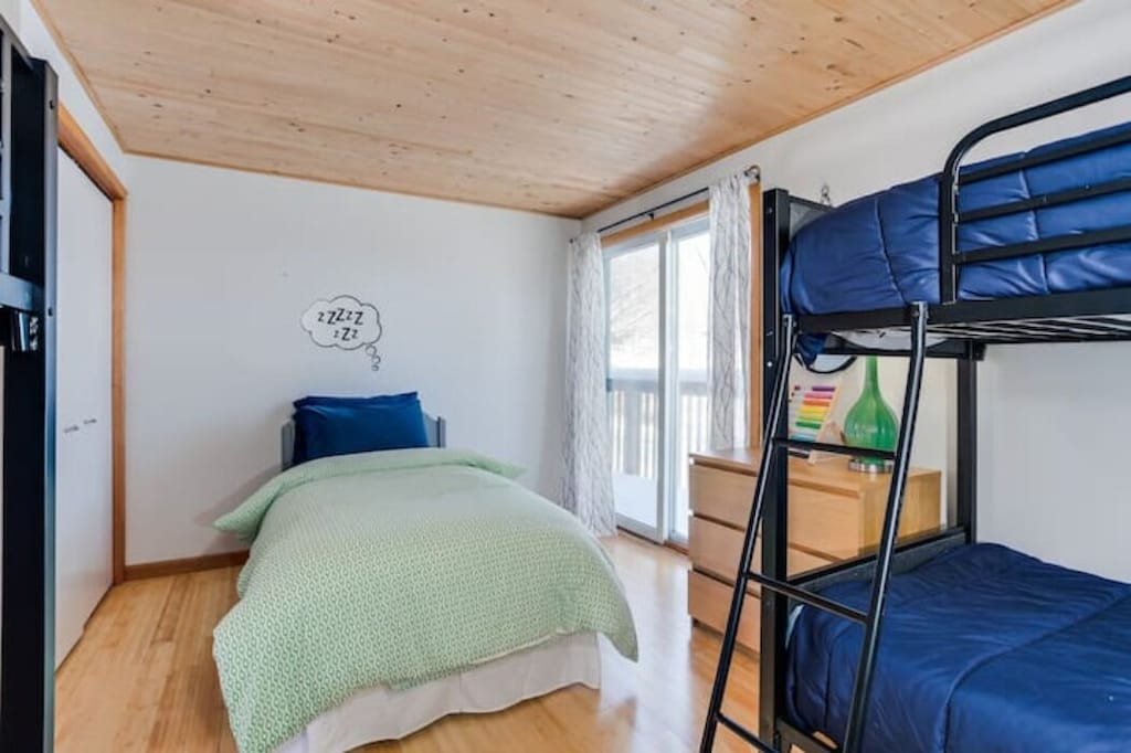 This bedroom has a single bed, and two sets of bunks, one of which you see here