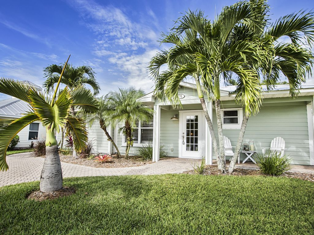 Lush green grass and palm trees surround our Bay Pointe Cottage.