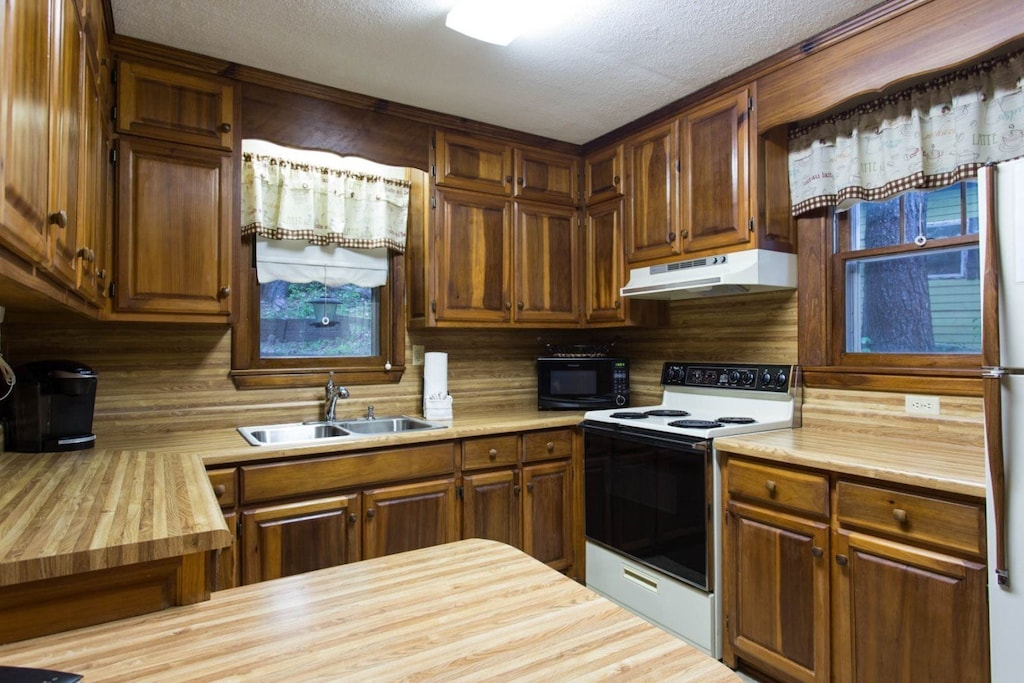In the kitchen is an electric range, refrigerator, microwave, coffee maker, and more. With no dishe you will enjoy the view from the window over the sink.