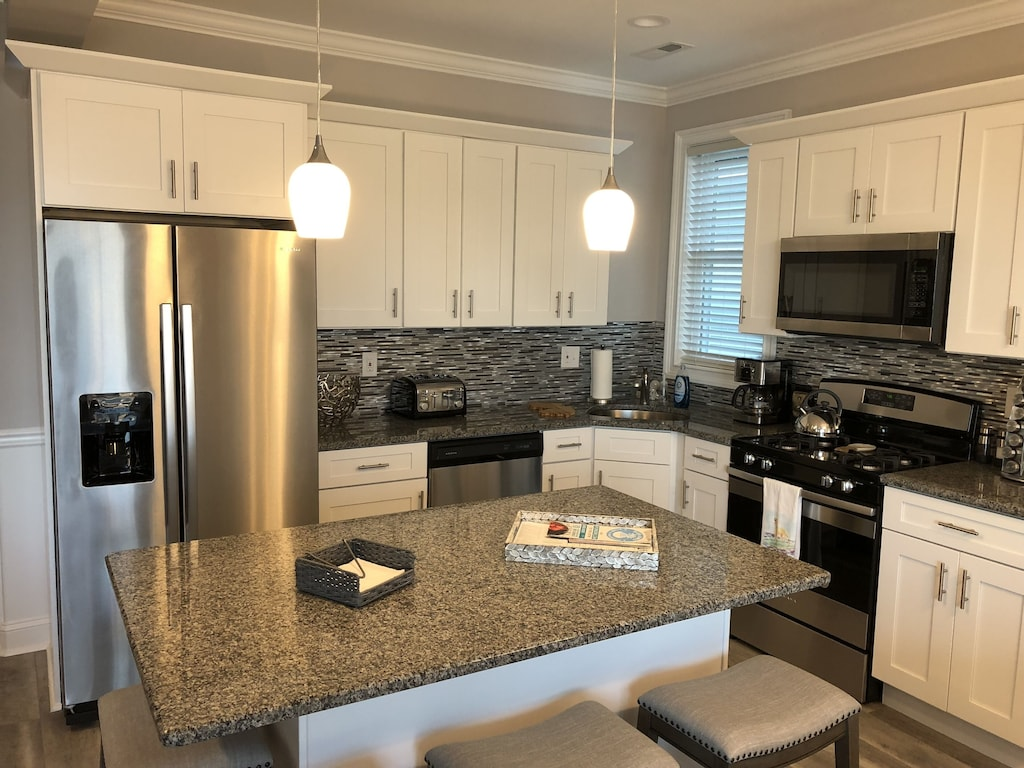Kitchen is stocked with amenities, granite counters & stainless steel appliances