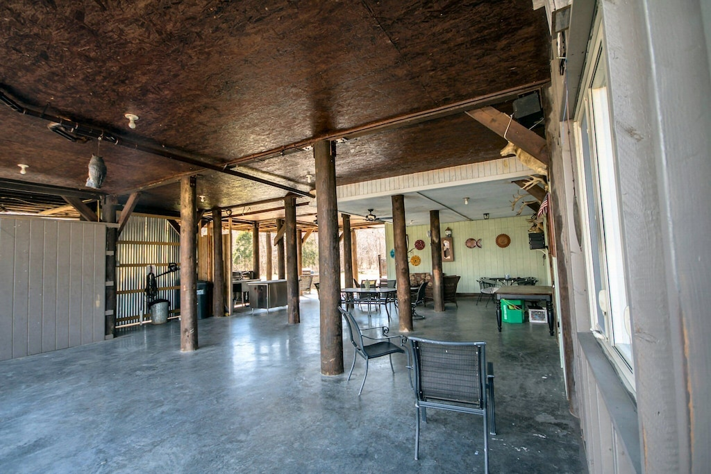 Huge hang-out area under house with high ceilings, sitting and eating space and covered parking