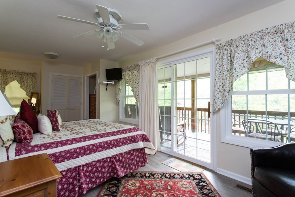 The windows along the wall of the room includes a sliding door for access to the lakeside deck.