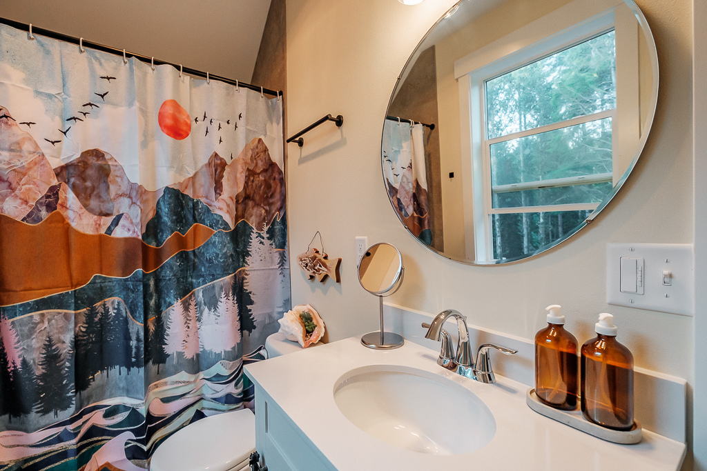Upper level bathroom with forest views.