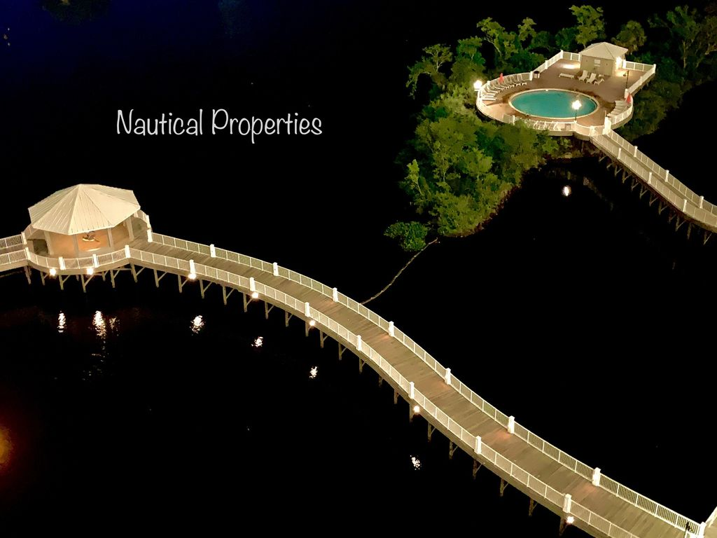 Your view of the lake, island pool and gazebo is beautiful at night.