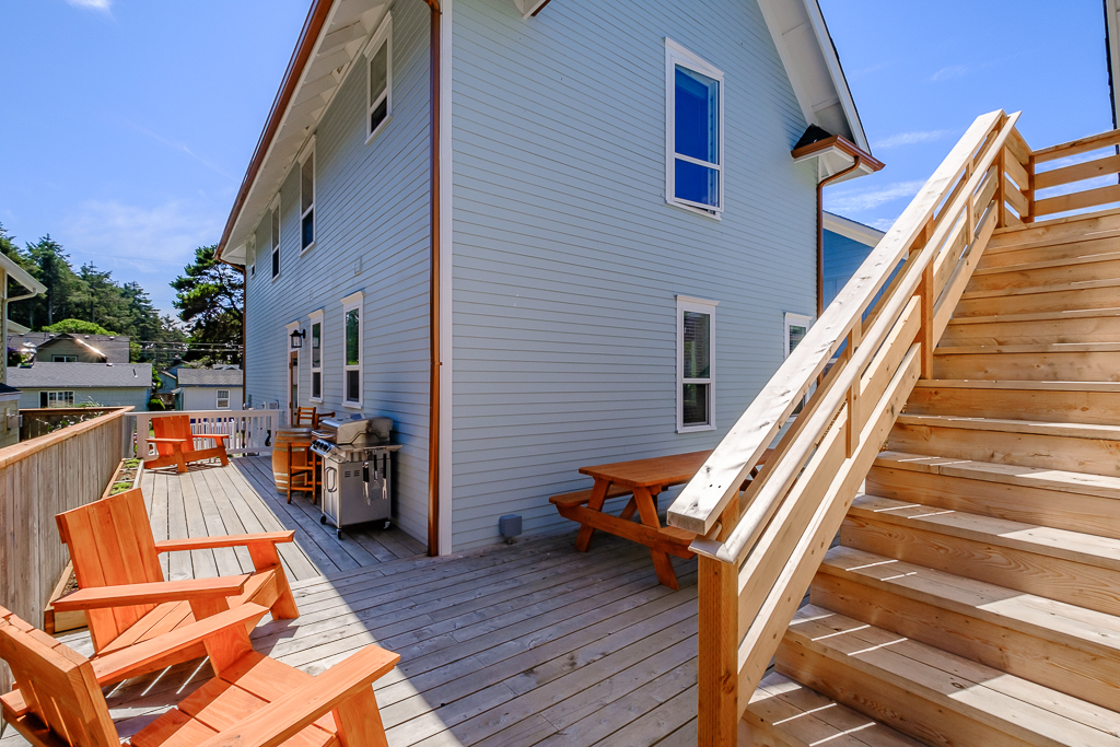 Back Porch area, with seating, picnic table, propane grill, and stairs to optional add-on Mother-in-law suite.