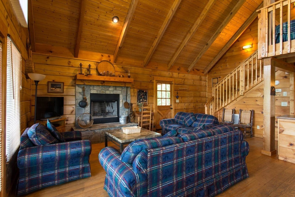 In the living area is comfortable furnishings, a TV, and a stone beautiful fireplace.