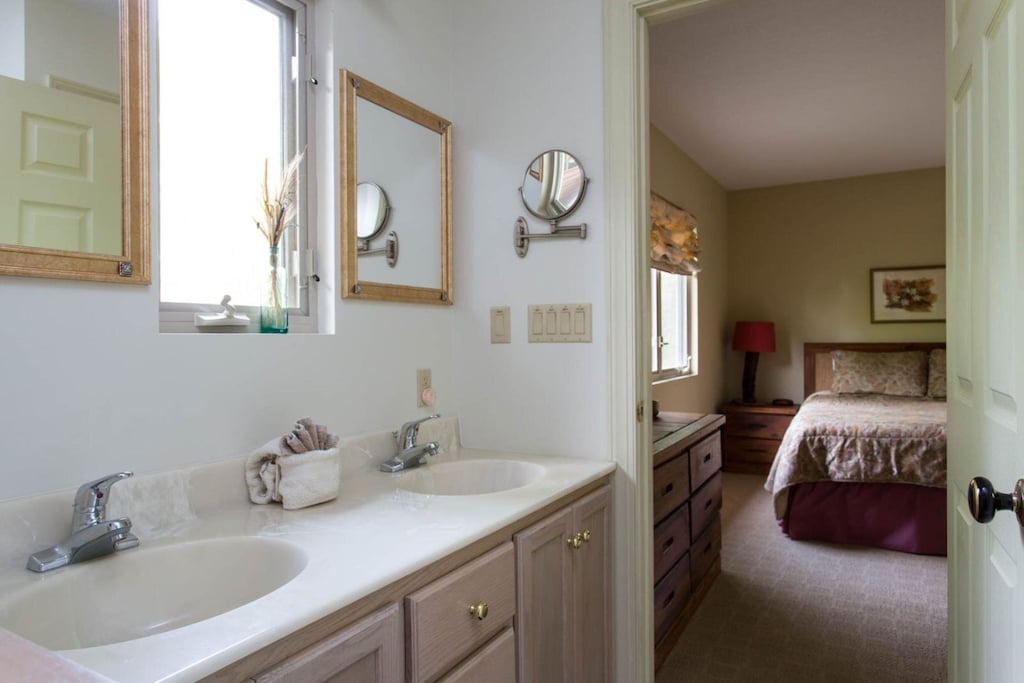 A window about the vanity, between the sinks, lets in plenty of natural light.
