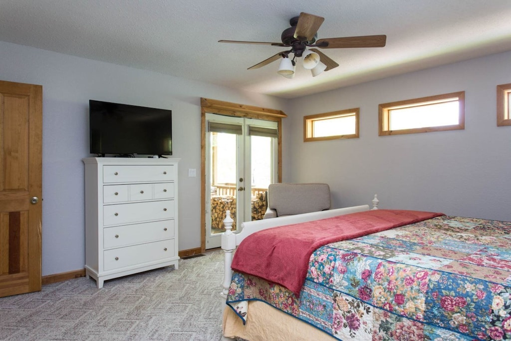 This bedroom offers a ceiling fan and TV. Access the covered porch via the French doors.