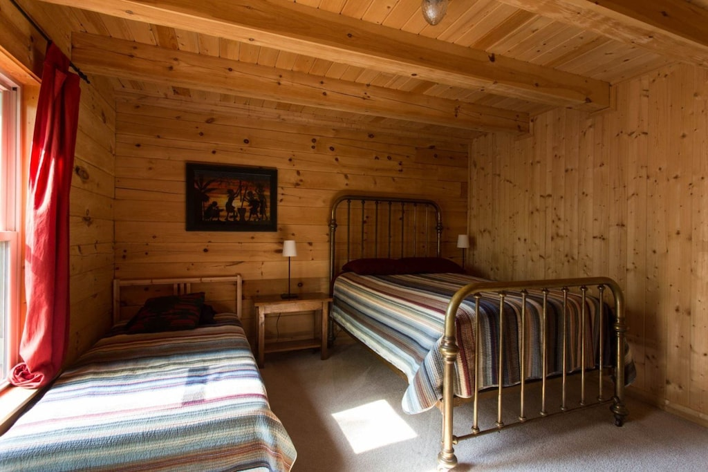 Down the hall from the kitchen, is a bedroom with a full and twin bed.
