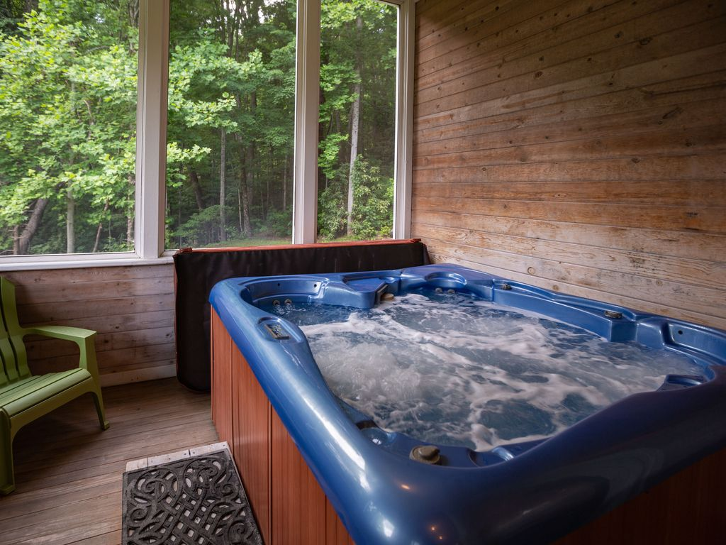 Relax in the hot tub on screened porch.