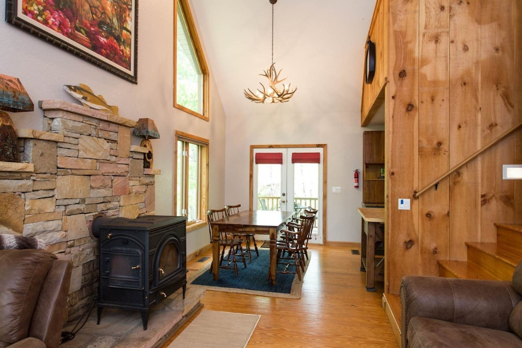 Between the living and dining areas is a wood-burning stove, with windows reaching to the roof peak on either side.