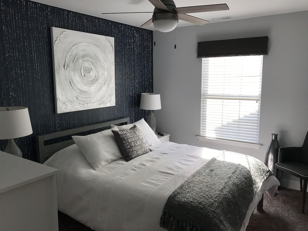 """First bedroom beautifully designed with a queen bed, chair, dresser and 43"""" TV"""