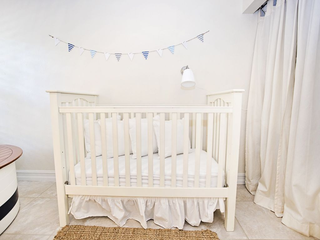 Guest bedroom with a baby crib as well as a trundle with 2 twin size mattresse