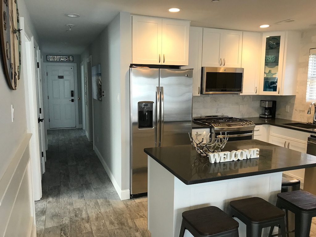 Kitchen has new stainless steel appliances, quartz countertops and open island