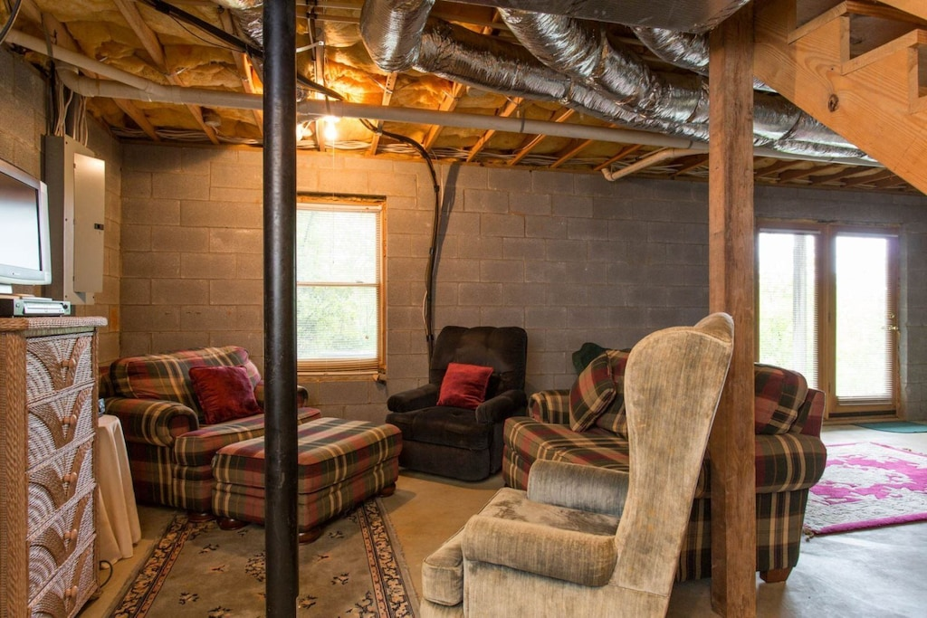 In the unfinished basement is a sofa, chairs, bureau, TV, and French doors that lead to the outdoors.