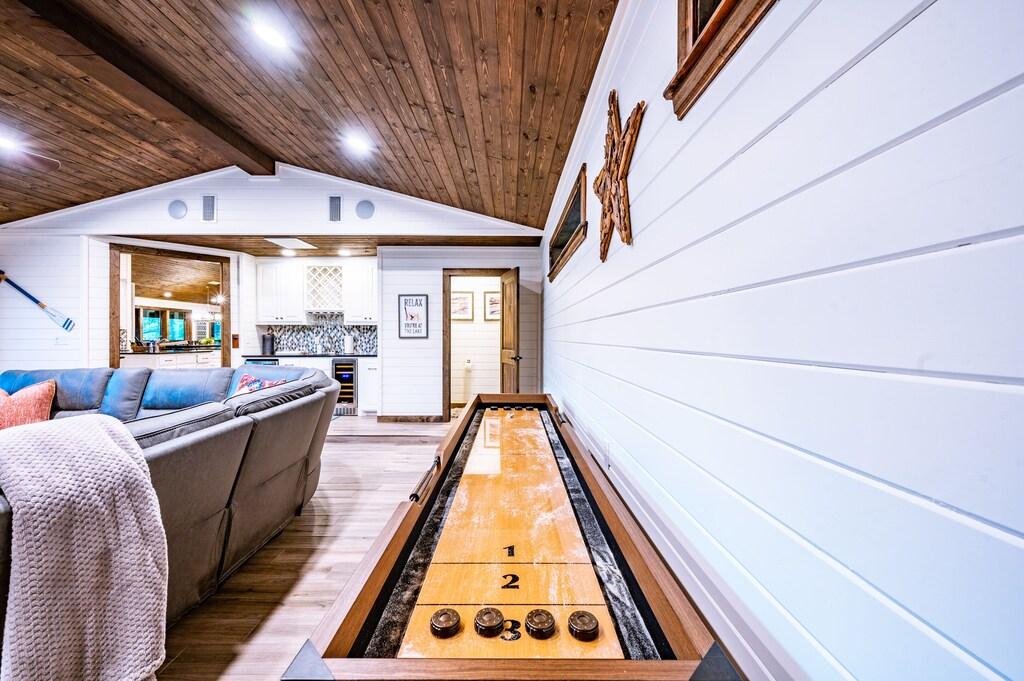 Game room has a shuffle board, huge sectional, bar area, and a half bath.