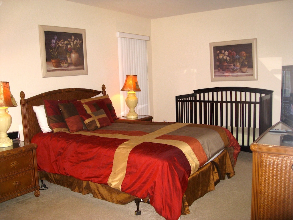 Queen bedroom with large smart TV and crib