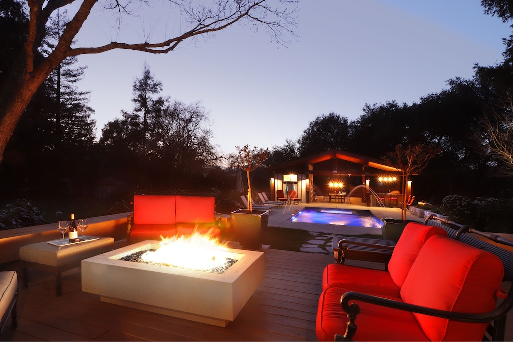 Deck fire feature and pool at dusk.