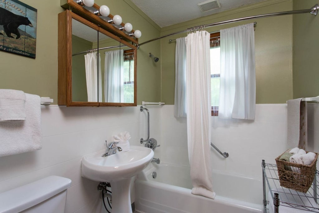 The home has a full bath with a pedestal sink and bathtub/shower combination.