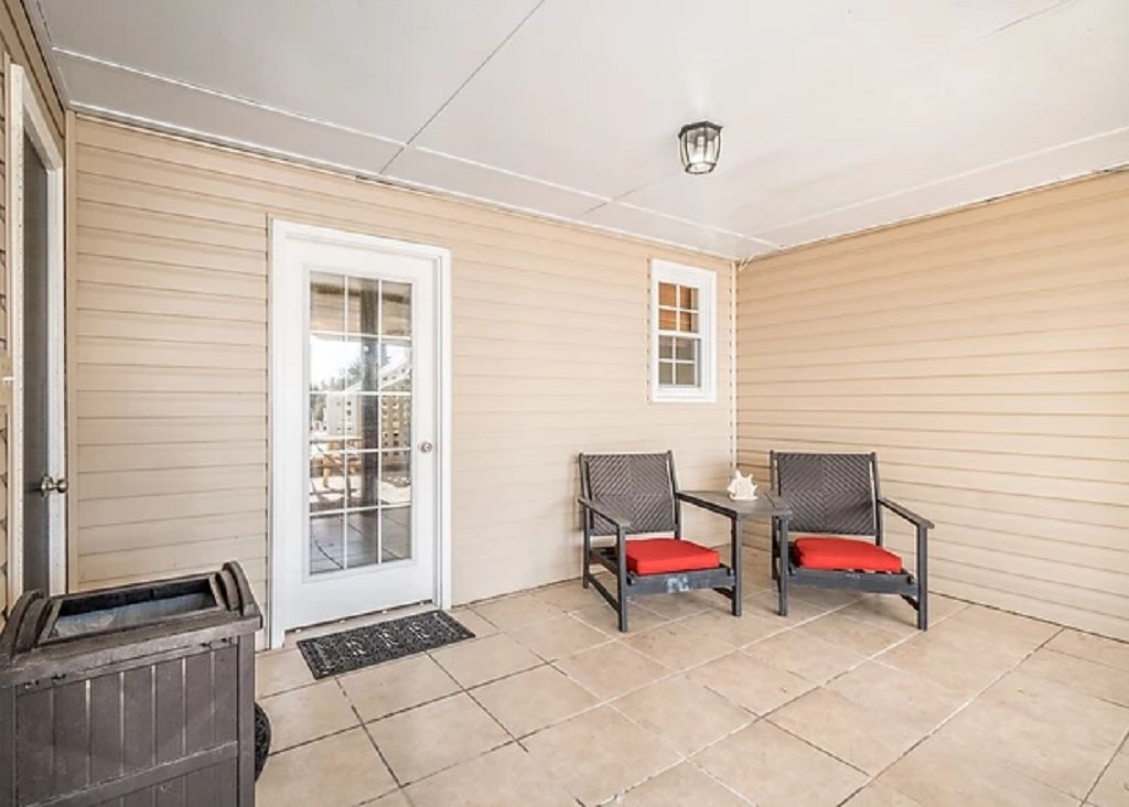 Seating area under the covered porch outside the pool table room and pool deck