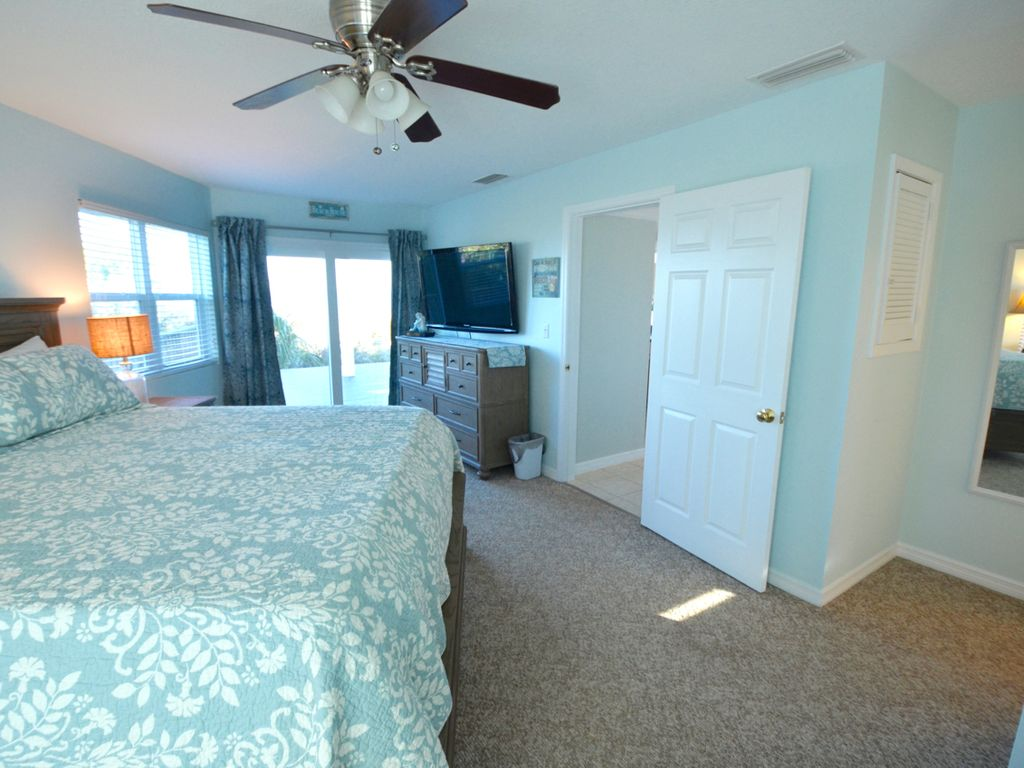 """Master bedroom with private porch access, 55"""" TV and full length mirror."""