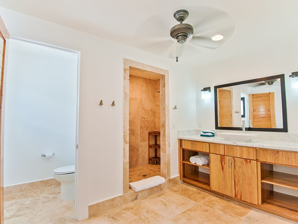 Spacious bathrooms with private toilets and a rainfall shower.