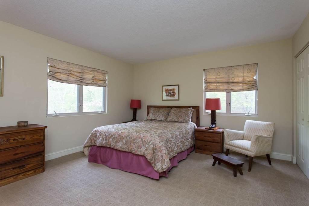 The queen bed suite is spacious and features windows and a comfortable chair.